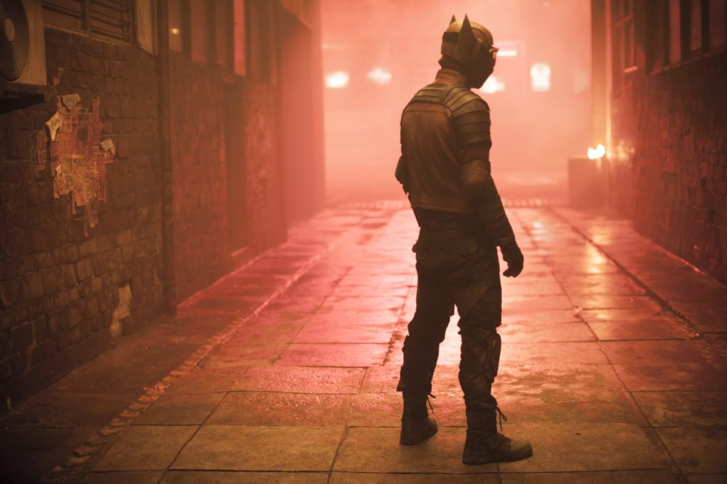 Den Rücken zu Kamera gewandt, steht Gundala in einer Gasse. Das rote Licht passt farblich zu seinem Superheldenkostüm.