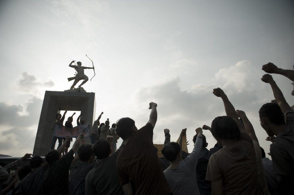 DIe Bürger Indonesiens stecken ihre Fauts siegreich zum Himmel