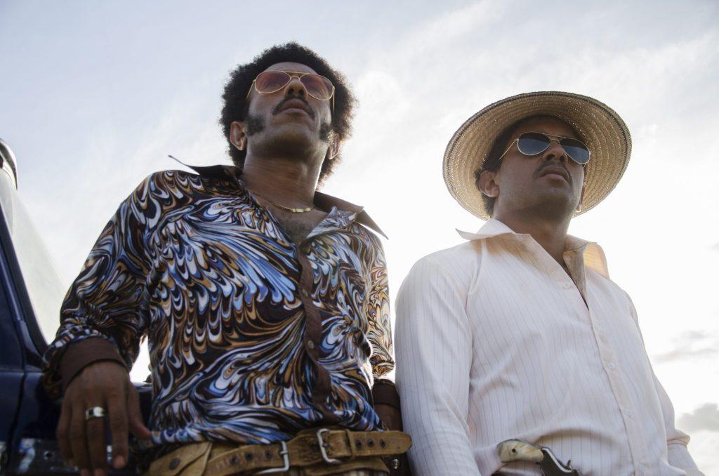 José Acosta als Rapayet und Jhon Narváez als Moisés lehnen sich an ein Auto in Birds Of Passage