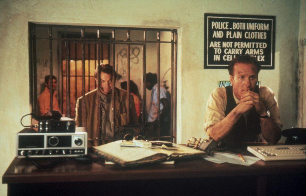 Nachdem sie sich geprügelt haben, sitzen Fitzpatrick, gespielt von Sam Neill, und Farber gespielt von William Hurt, in Bis ans Ende der Welt im Knast. Fitzpatrick lehnt in der Zelle mit seinem Kopf an den Gittern, während Farber davor am Pult der Polizisten stehend und seine Ellenbogen darauf stützend seine Aussage macht.