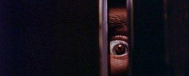 Ein Auge starrt durch einen Türspalt