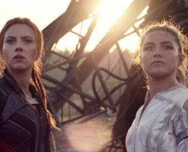 Natasha (Scarlett Johansson) und Yelena (Florence Pugh) stehen vor einem brennenden Wrack. Natasha hat rote Haare und trägt ein dunkles Outfit, Yelena ein weißes Kostüm.