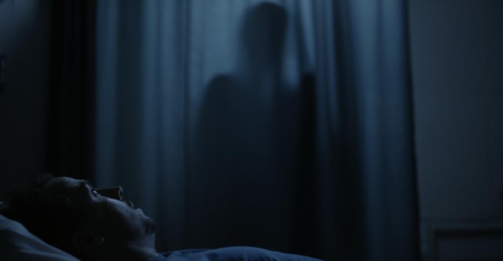 Frankie Muniz liegt im Bett. Im Hintergrund sieht man einen Schatten hinter einem Vorhang in The Black String.