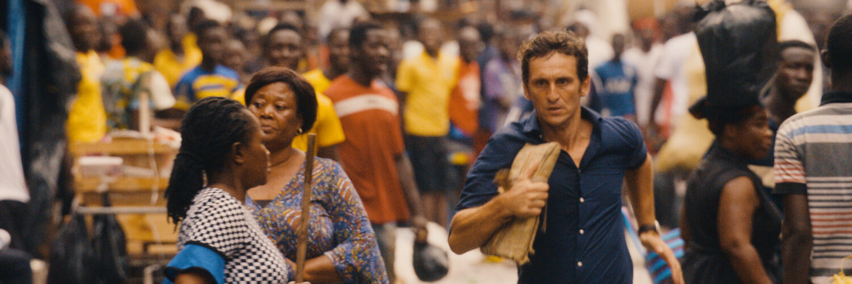 Carlos, gespielt von Raúl Arévalo, flüchtet mit den Dokumenten durch die Menge.