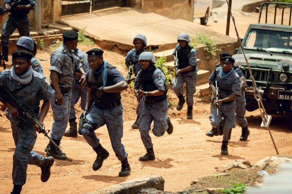 Mit Maschinengewehren bewaffnete Soldaten des korrupten Regimes stürmen den Slum.