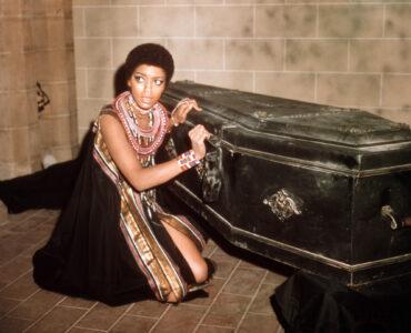 Luva (Vonetta McGee) kniet in einem schwarzen Kleid mit viel Schmuck neben einem schwarzen Sarg und schaut schockiert an der Kamera vorbei.