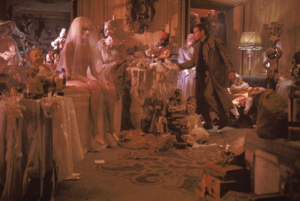 Deckard sucht nach der Replikantin Pris (Daryl Hannah), die sich, perfekt angepasst an die Puppen im Wohnzimmer, unter einem Brautkleid versteckt - Der Blade Runner