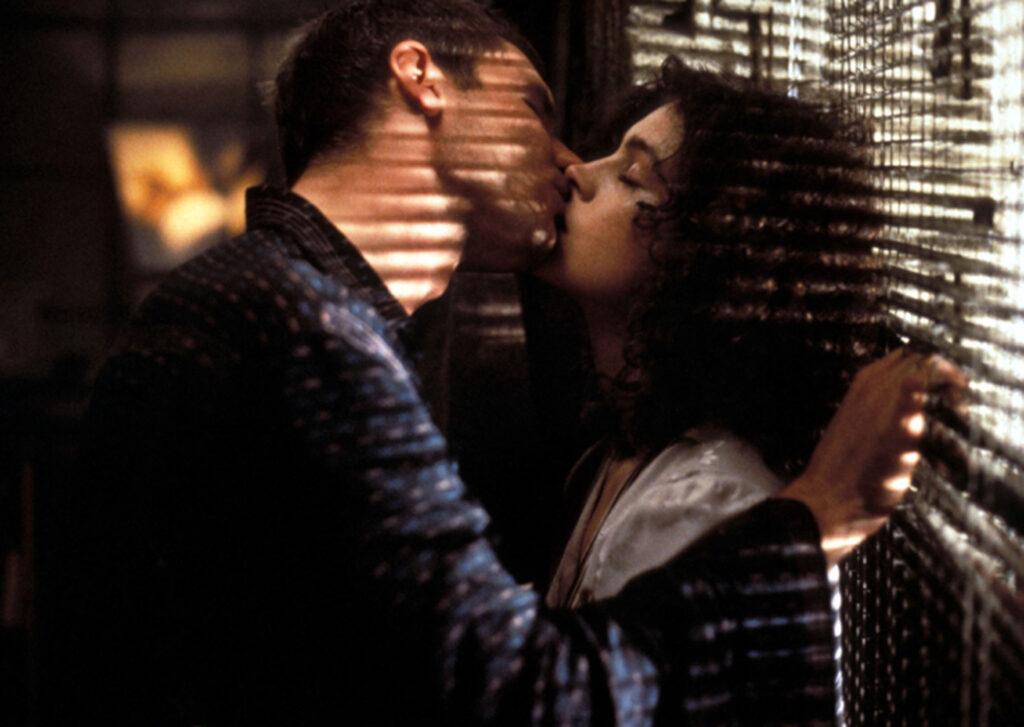 Vor dem diffusen Licht, das hinter ihnen durch eine Jalousie hineinfällt, küssen sich Deckard und Rachael leidenschaftlich - Der Blade Runner