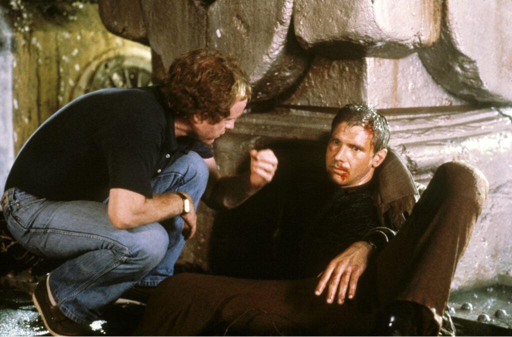 Harrison Ford lehnt liegend und in seiner Rolle verharrend gegen ein großes Requisit, während Ridley Scott vor ihm kniet, um ihm letzte Anweisungen zu geben - Der Blade Runner