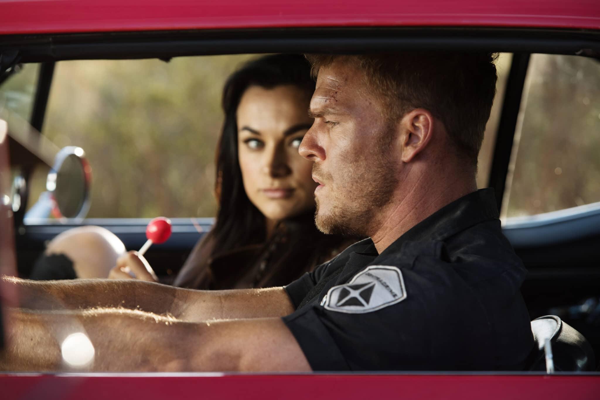 """Christina Ochoa als Grace d'Argento, die auf dem Beifahrersitz eines Autos sitzt und einen Lolli in der Hand hält, blickt Alan Ritchson als Arthur Bailey an, der neben ihr sitzt und auf die Straße schaut in """"Blood Drive""""."""