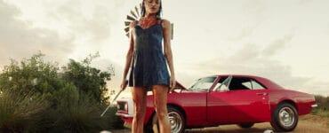 """Christina Ochoa als Grace steht in """"Blood Drive"""" blutbespritzt und in einem blauen Kleid über der Leiche eines Mannes. Sie hält einen spitzen Metallstab in der Hand und im Hintergrund ist ihr rotes Auto zu sehen."""