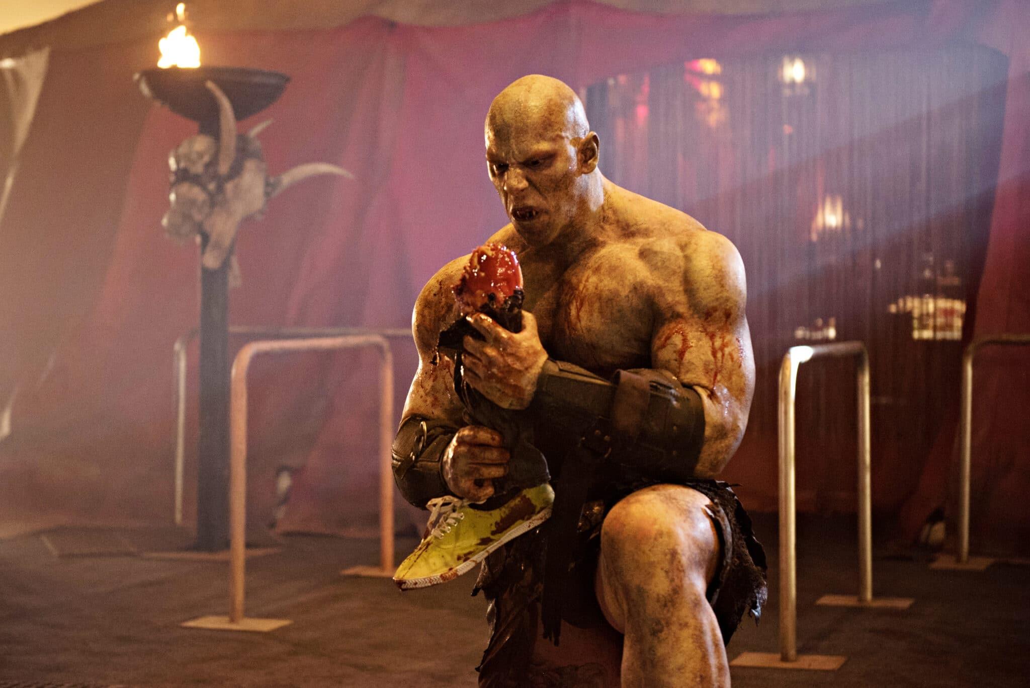 """Der muskelbepackte, kahlköpfige Dämon Denali (Martyn Ford) steht in """"Blood Drive"""" vor einem Zelt und hält ein abgetrenntes Bein in den Händen."""