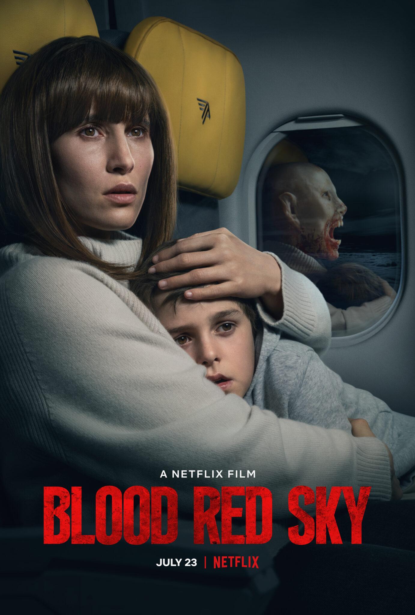Das Plakat des Films Blood Red Sky zeigt die Protagonistin Nadja neben ihrem Sohn Elias auf zwei Sitzen im Flugzeug. Im Hintergrund sieht man eine Fensterscheibe, in der ein blutiges Vampirgesicht statt einer normalen Spiegelung zu sehen ist.