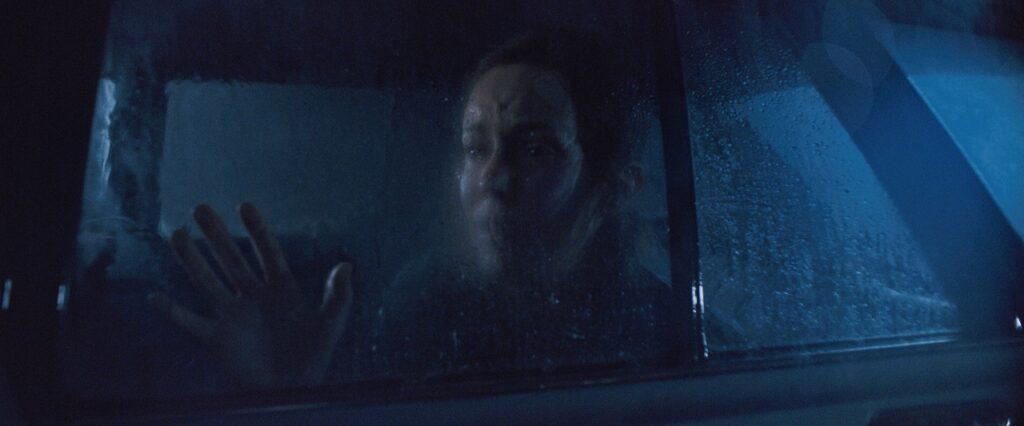 Hilfos schaut Bethany Anne Lind im bläulichen Mondschein der regnerischen Nacht aus dem Fenster ihres Autos - Blood on My Name