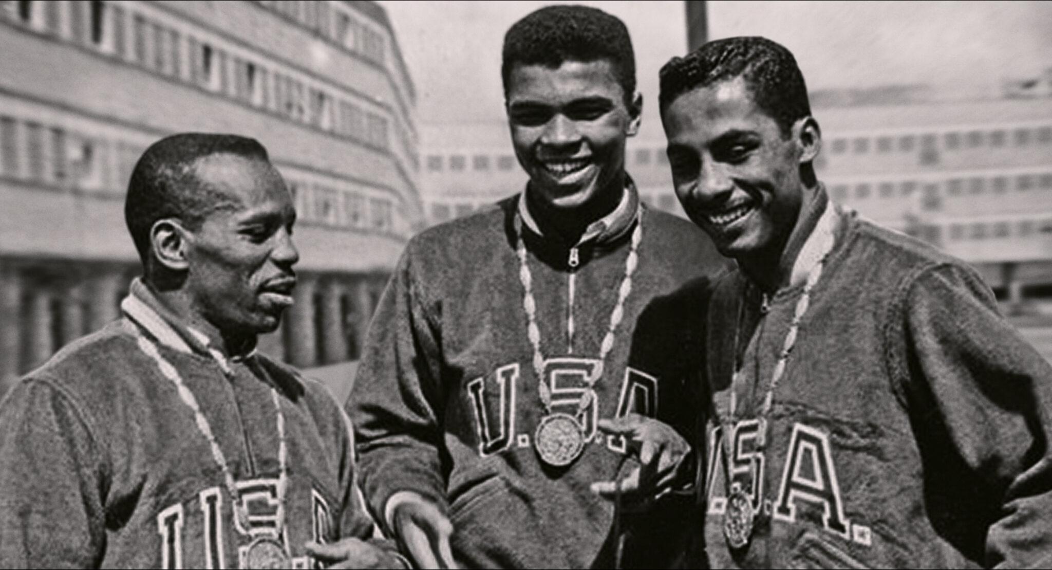Eine Schwarzweißaufnahme mit Muhammad Ali in der Mitte zwischen zwei weiteren Afroamerikanern. Alle haben Nationaltrikots an und Medaillen um den Hals