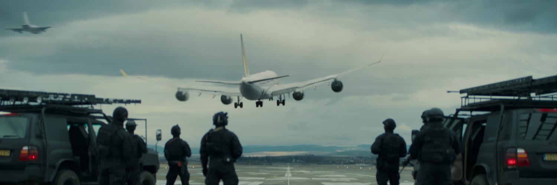 Das Bild aus Blood Red Sky zeigt ein Flugzeug von hinten über der Landebahn. Außerdem sieht man im Vordergrund einige bewaffnete Personen sowie zwei gepanzerte SUVs