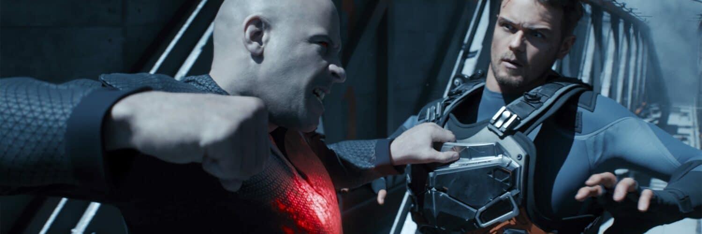 Bloodshot (Vin Diesel) attackiert mit einer leuchtend roten Hand einen Angreifer in Kampfanzug vor einem Autowrack.