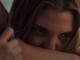 Eine Frau mit merkwürdiger Augenfarbe beißt in den Hals einer anderen Person