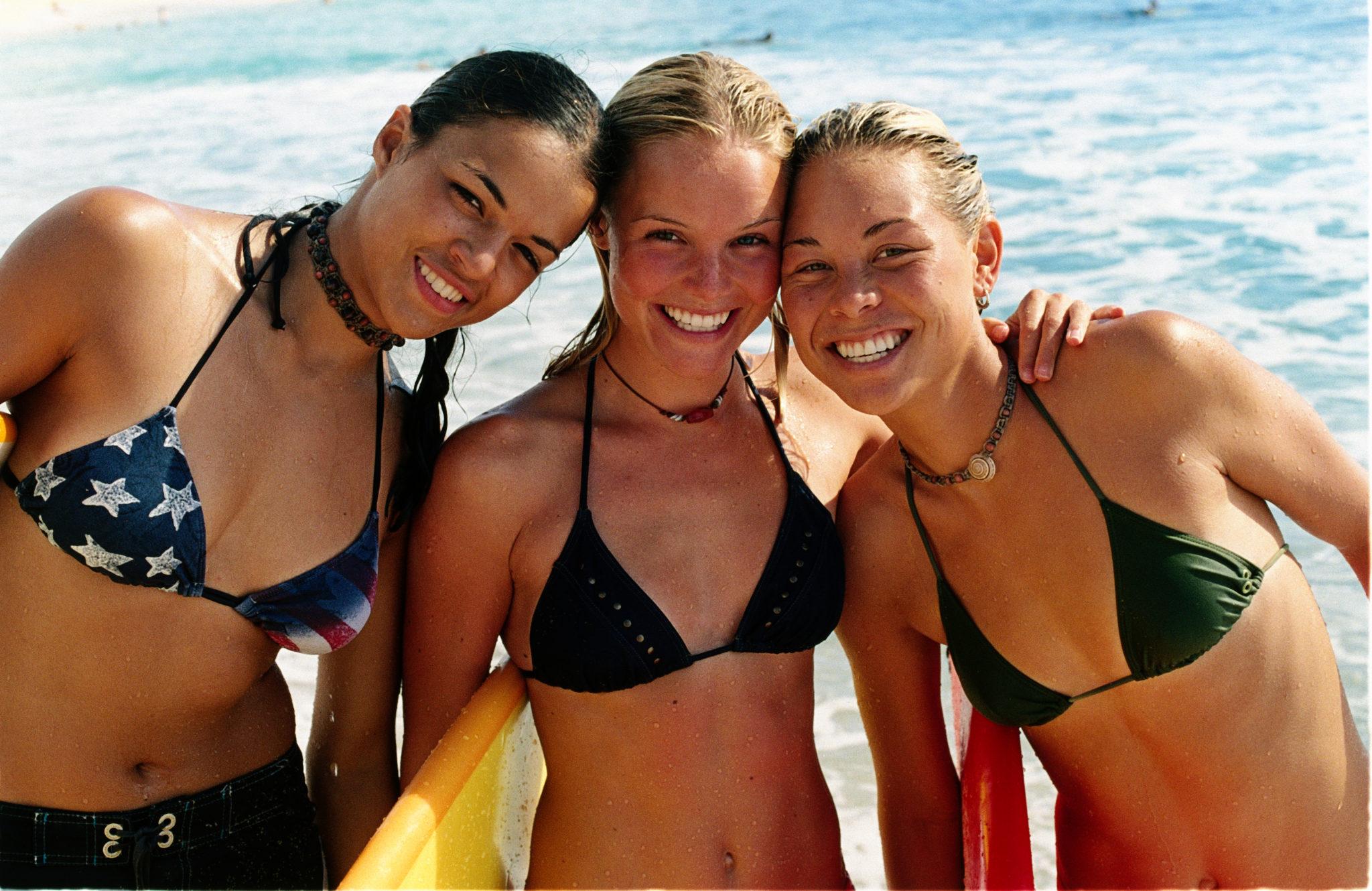 """Michelle Rodríguez als Eden, Kate Bosworth als Anne Marie und Sànoe Lake als Lena stehen in Bikinis am Strand und blicken grinsend in die Kamera in """"Blue Crush""""."""