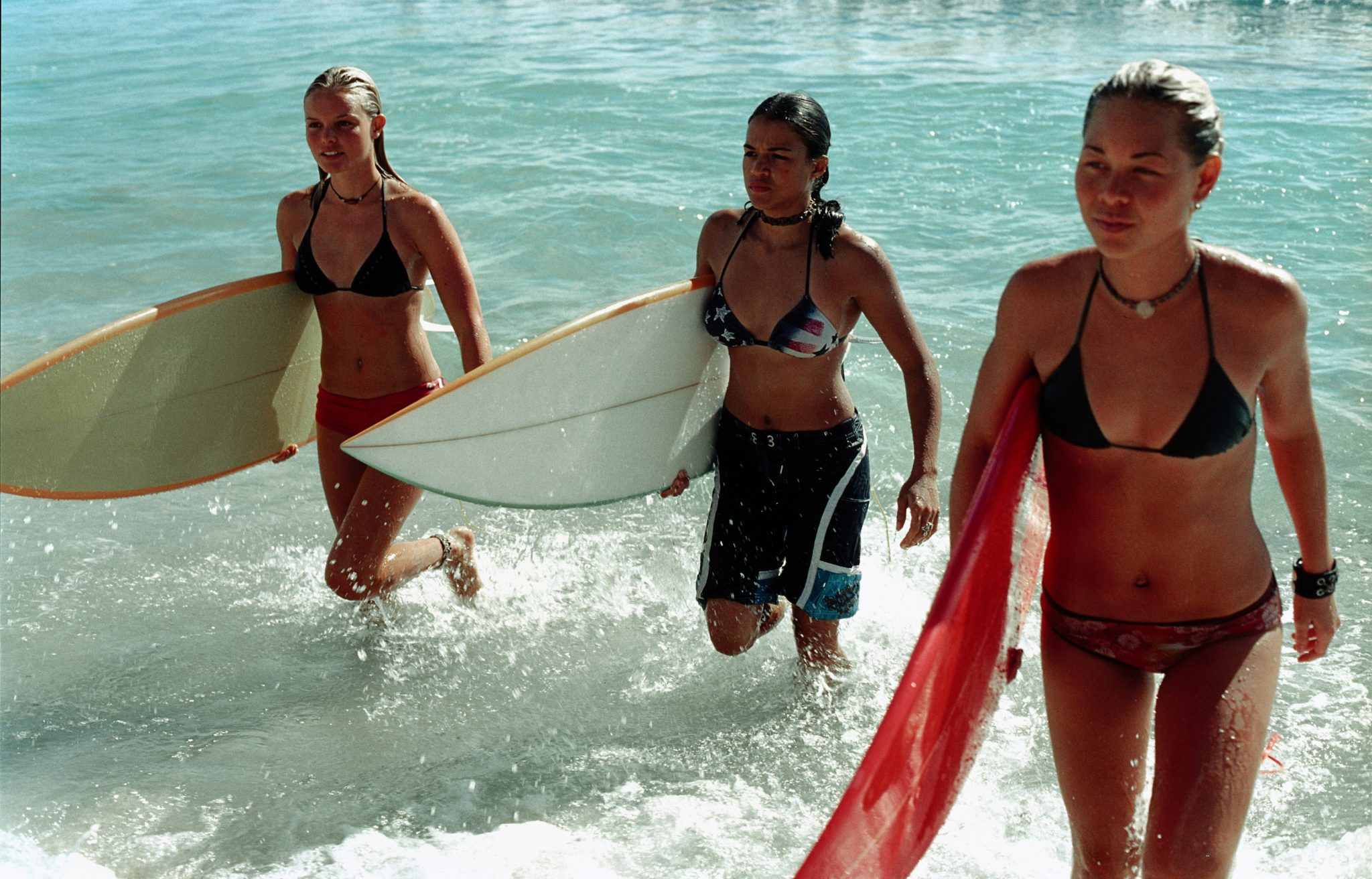 """Kate Bosworth als Anne Marie, Michelle Rodríguez als Eden und Sànoe Lake als Lena steigen mit ihren Surfbrettern in der Hand vom Meer ans Land zurück in """"Blue Crush""""."""