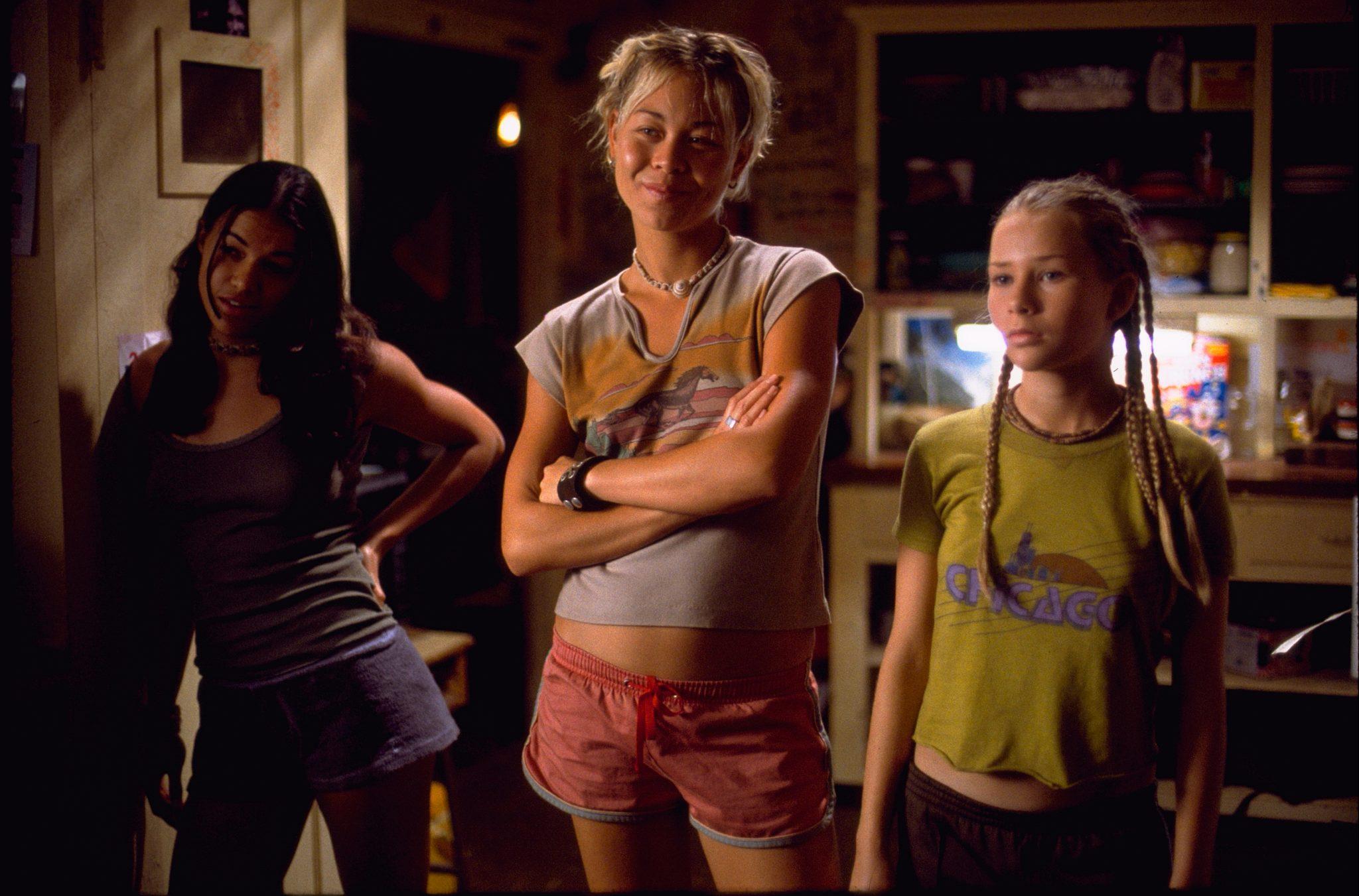 """Michelle Rodríguez als Eden, Sànoe Lake als Lena und Mika Boorem als Penny blicken amüsiert und erwartungsvoll in ihrer Hütte auf Anne Marie, die außerhalb des Bildes steht in """"Blue Crush""""."""