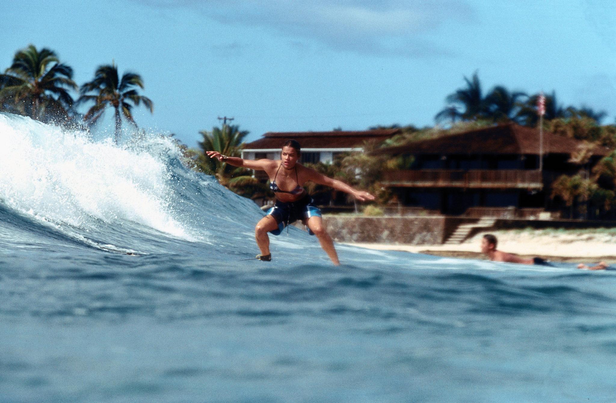 """Michelle Rodríguez als Eden surft in """"Blue Crush"""" mir unsicherem Blick auf einer Welle."""