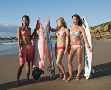 """Elizabeth Mathis als Pushy, Sasha Jackson als Dana und Sharni Vinson als Tara stehen in Bikinis und Badeanzügen mit ihren Surfbrettern am Strand und blicken in die Sonne in """"Blue Crush 2""""."""
