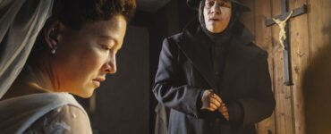 Hannah Herzsprung als Gefi schaut bestürzt, während Michael Herbig als Boandlkramer im schwarzen Anzug gespannt wartet - Neu bei Prime im Mai 2021