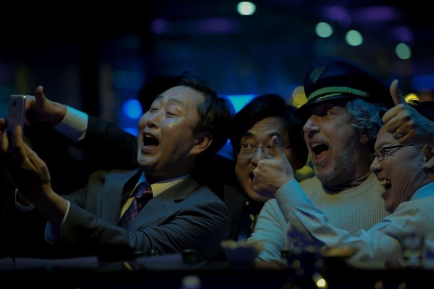 """Alain Chebat steht als Stéphane am rechten Bildrand inmitten einer Gruppe angetrunkener südkoreanischer Geschäftsmänner, trägt eine Kapitänsmütze und macht mit ihnen ein Selfie in """"Bon Voyage""""."""