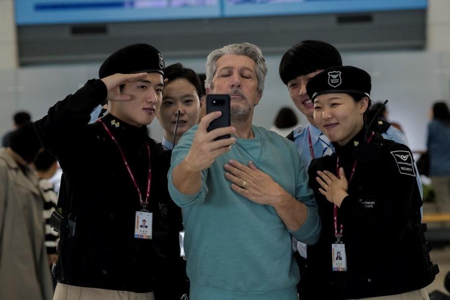 """Alain Chabat steht als Stéphane inmitten einer Gruppe südkoreanischer Flughafen-Mitarbeiter und macht mit ihnen ein Selfie in """"Bon Voyage""""."""