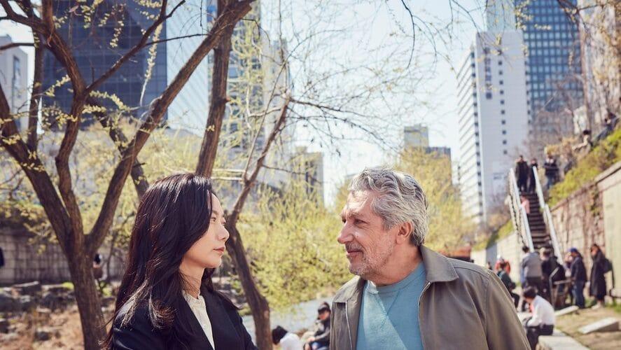 """Doona Bae als Soo und Alain Chabat als Stéphane stehen inmitten des Stadtparks von Seoul in """"Bon Voyage"""" und blicken einander an."""