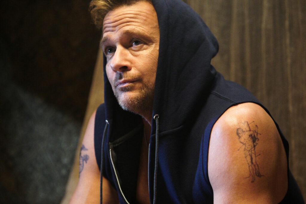 Mickey Kelley (Sean Patrick Flanery) vor dem Kampf im ärmellosen Hoodie mit entspannten Blick. - Born a Champion