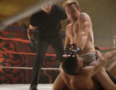 Mickey (Sean Patrick Flanery) gewinnt die Oberhand in einem Kampf. Er sitzt auf der Brust seines Gegners, versucht dessen Kopf mit der linken Hand nach unten zu drücken und diesen zu besiegen. Daneben steht noch ein Ringrichter, der das Geschehen beobachtet. - Born a Champion