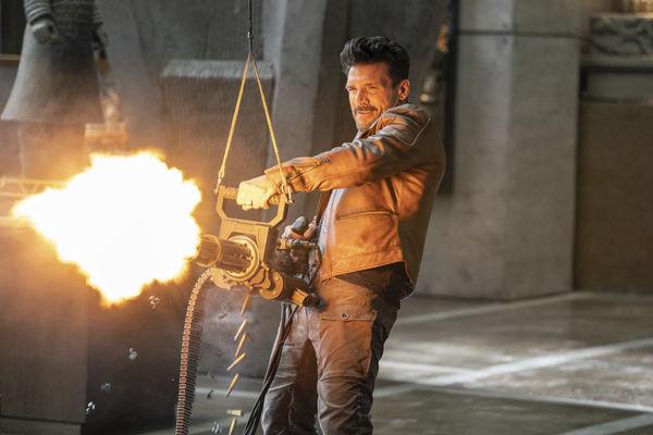 """Roy Pulver (Frank Grillo) steht mit einem großen Maschinengewehr in einem großen Raum und feuert beidhändig aus allen Rohren. - """"Boss Level"""""""