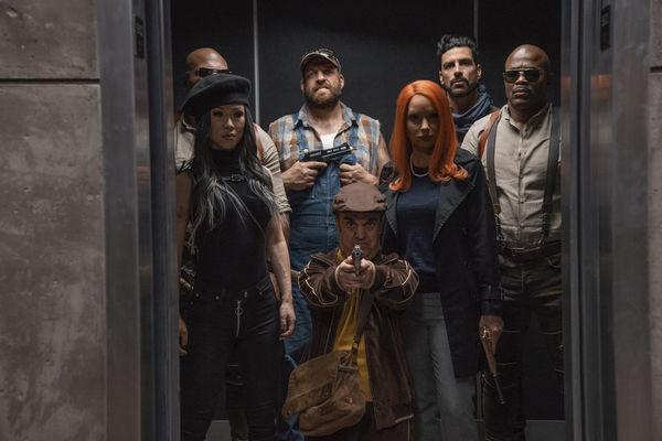 """In einem Aufzug steht die Killer-Brigade aus """"Boss Level"""" gemeinsam. Dazu gehören mehrere Männer, von denen beispielsweise einer mit Latzhose gekleidet ist oder ein kleinwüchsiger Mann in Jogginganzug, der eine Pistole in beiden Händen hält und auf den Betrachter richtet. Darüber hinaus sind auch Frauen im Aufzug, von denen eine Asiatisch ist und die anderen feuerrotes Haar hat."""