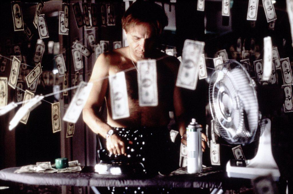 Joe Pantoliano als Caesar bügelt Dollarnoten