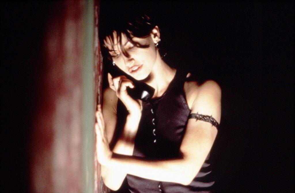 Gina Gershon als Corky mit dem Telefonhörer in der Hand.