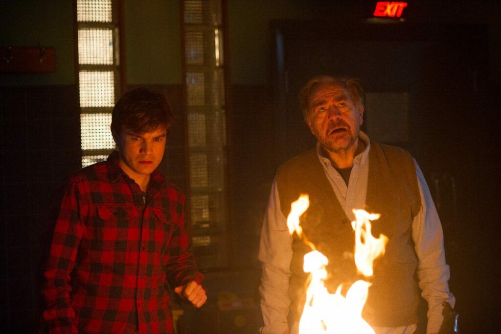 Emil Hirsch und Brian Cox stehen in The Autopsy of Jane Doe, die erste Empfehlung unserer gruseligsten Hexenfilme, vor einem Feuer und blicken darauf