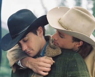 Jake Gyllenhaal wird in brokeback Mountain von Hinten von Heath Ledger umarmt, während beide warme Jacken und Cowboy-Hüte tragen