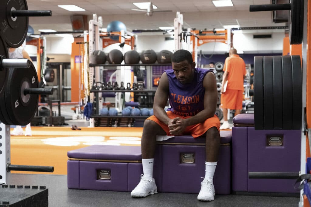 Ray Ray (Jay Reeves) sitzt in der Umkleidekabine der Clemson Tigers Footballmannschaft. Er trägt Sportkleidung in den Universitätsfarben Purpur und Orange. Er wirkt nachdenklich und grübelt vor sich hin.