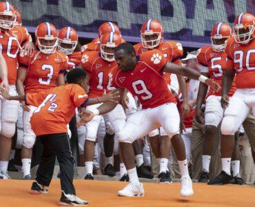 """Fay und Ray am berühmten """"The Hill"""" des Memorial Stadium der Clemson University, wo """"Bruderherz"""" spielt. Die beiden stehen sich gebeugt gegenüber und klatschen dynamisch mit den Händen in Hüfthöhe ein. Ray trägt seine Football-Kluft, während Fay lediglich ein einfach Dress trägt. Hinter ihnen steht die gesamte Footballmannschaft der Clemson Tigers."""