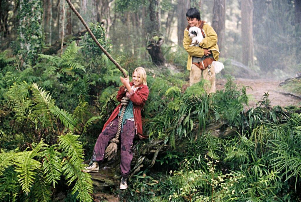 Leslie (AnnaSophia Robb) und Jess (Josh Hutcherson) schwingen sich an einem Seil über den Fluss, um nach Terabithia zu gelangen. Leslie steht am Ufer und hält das Seil, während Jess noch weiter oben am Rand steht und Leslie zuguckt. Dabei hält er einen Hund auf dem Arm.
