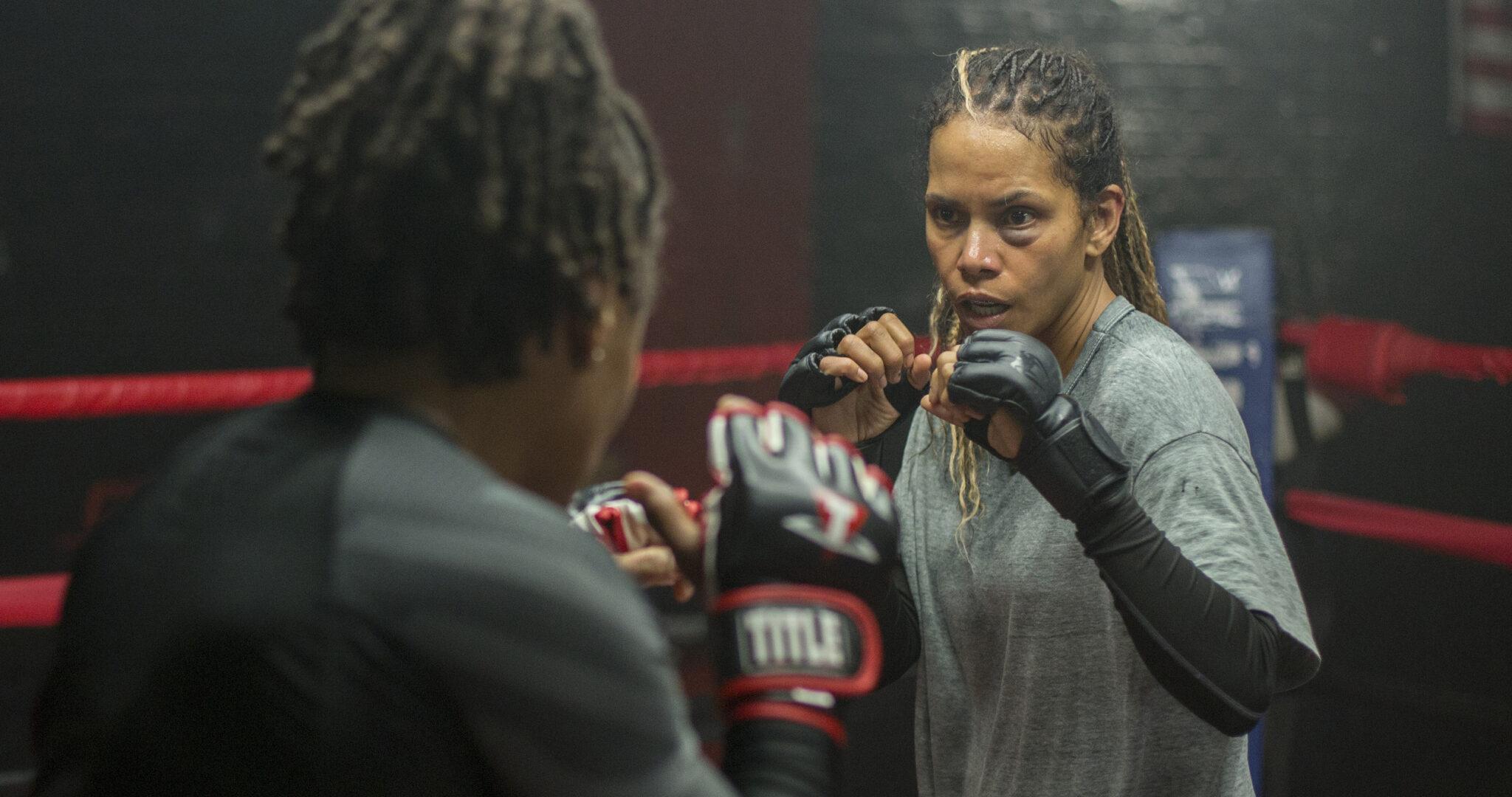 Halle Berry im Boxring mit Abwehrhaltung gegenüber einer weiteren Person, die man nur von hinten sieht.