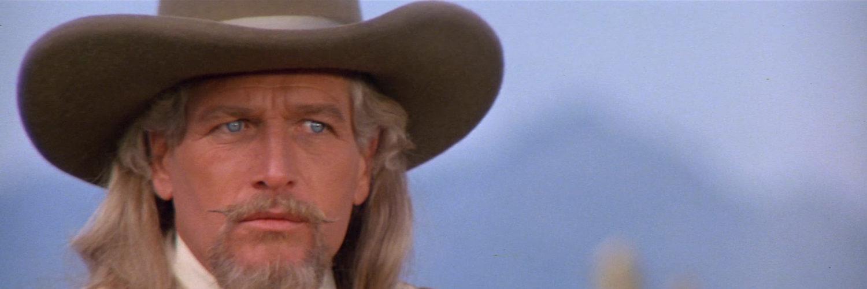 Paul Newman als Buffalo Bill in Nahaufnahme. Mit stilechtem Cowboy-Hut, imposanter Mähne, mächtigem Kinnbart und gezwirbeltem Schnauzer schaut er äußerst ernst drein.