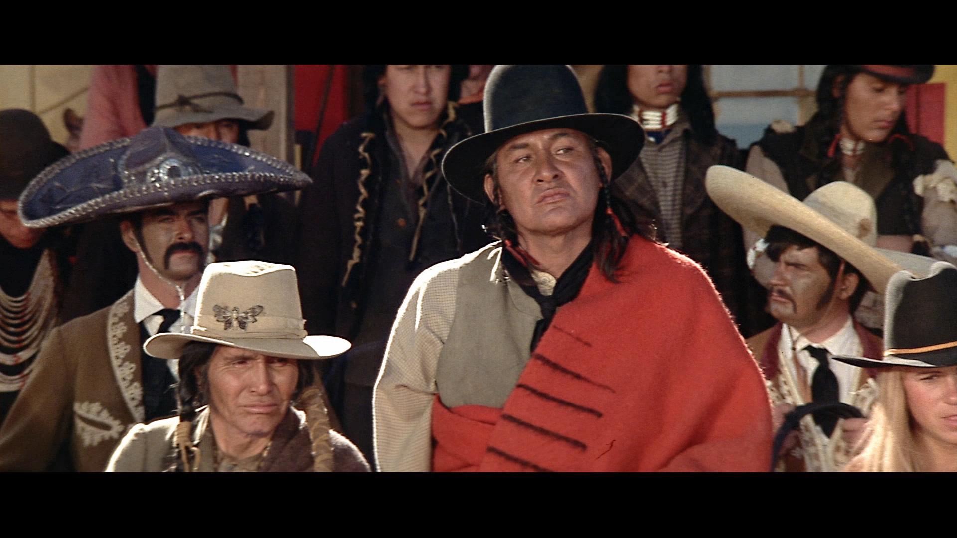 """Im Vordergrund sehen wir links Indianerhäuptling Sitting Bull und rechts dessen """"Interpretierer"""" William Halsey kritisch dreinblicken. Im Hintergrund sind einige Showmänner und -frauen zu sehen."""