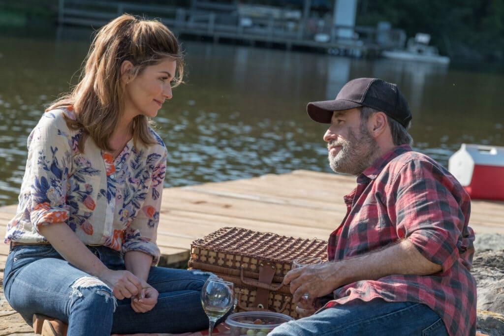 Sam, gespielt von John Travolta, und Becca, gespielt von Shania Twain, sitzen auf einem Holzsteg am See. Neben ihnen ein Picknickkorb, zwischen ihnen steht ein Weinglas.