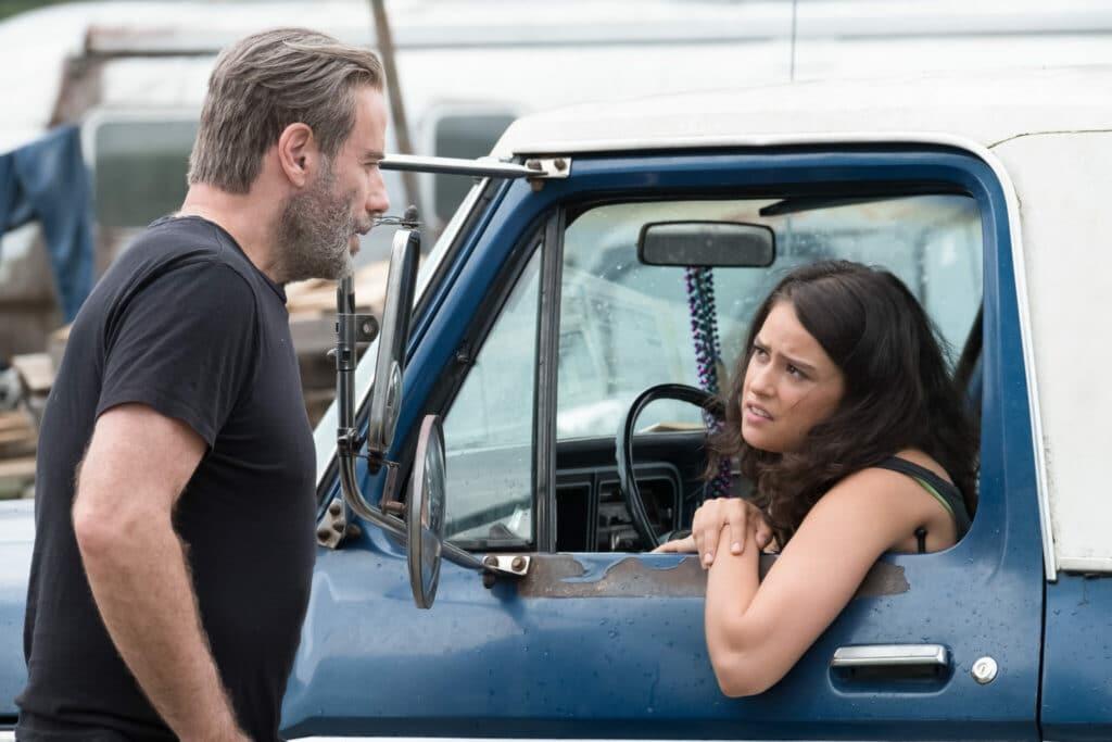 Sam Munroe, gespielt von John Travolta, spricht in Burning Speed - Sieg um jeden Preis mit Cams Frau Cindy, gespielt von Rosabell Laurenti Sellers, die am Steuer eines Pick-ups sitzt.