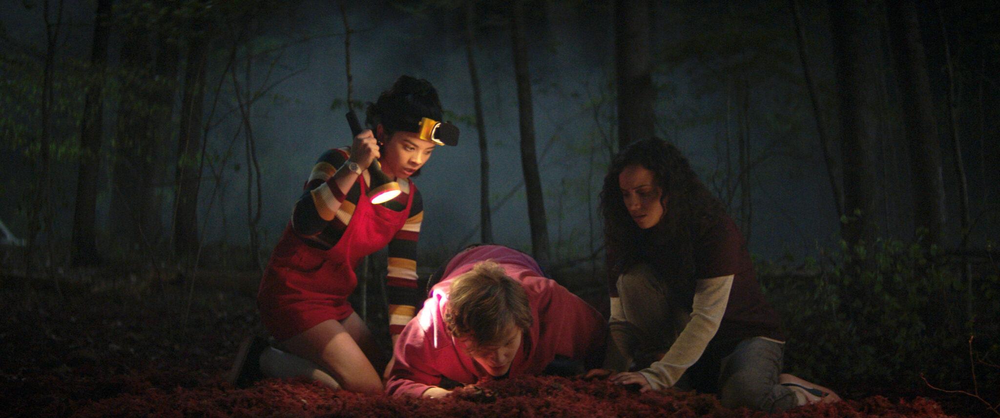 Kate, Simon und Deena knien in Fear Street Teil 1 im Wald nachts über einem Haufen roter Erde und suchen darin nach etwas.