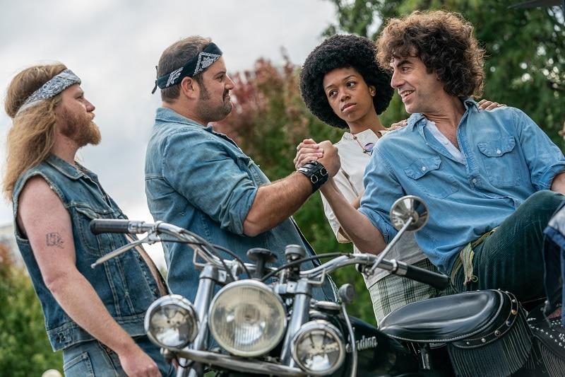 Zwei Motorradrocker stehen vor einem Mann und einem afro-amerikanischen Jungen; einer davon schlägt mit dem erfreuten Mann ein in The Trial of the Chicago 7 - Neu auf Netflix im Oktober 2020