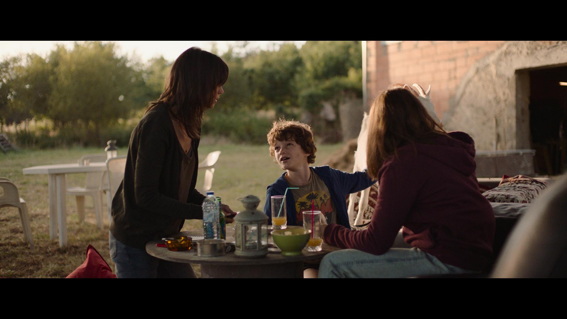Virginie und ihre beiden Kinder am Frühstückstisch vor dem Haus - Schwarm der Schrecken